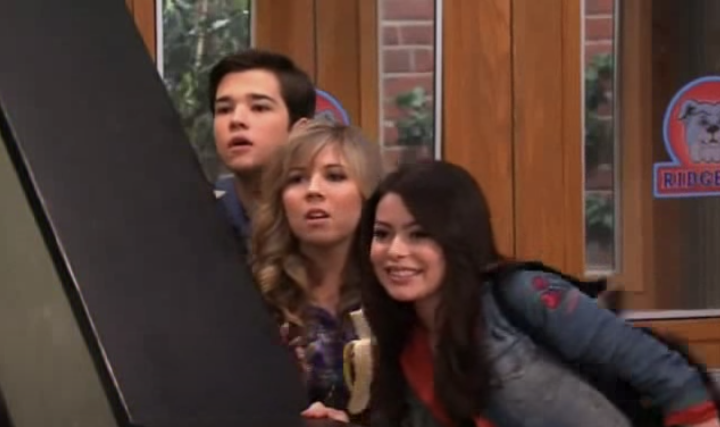 Carly, Freddie, and Sam hiding behind a stairwell at school