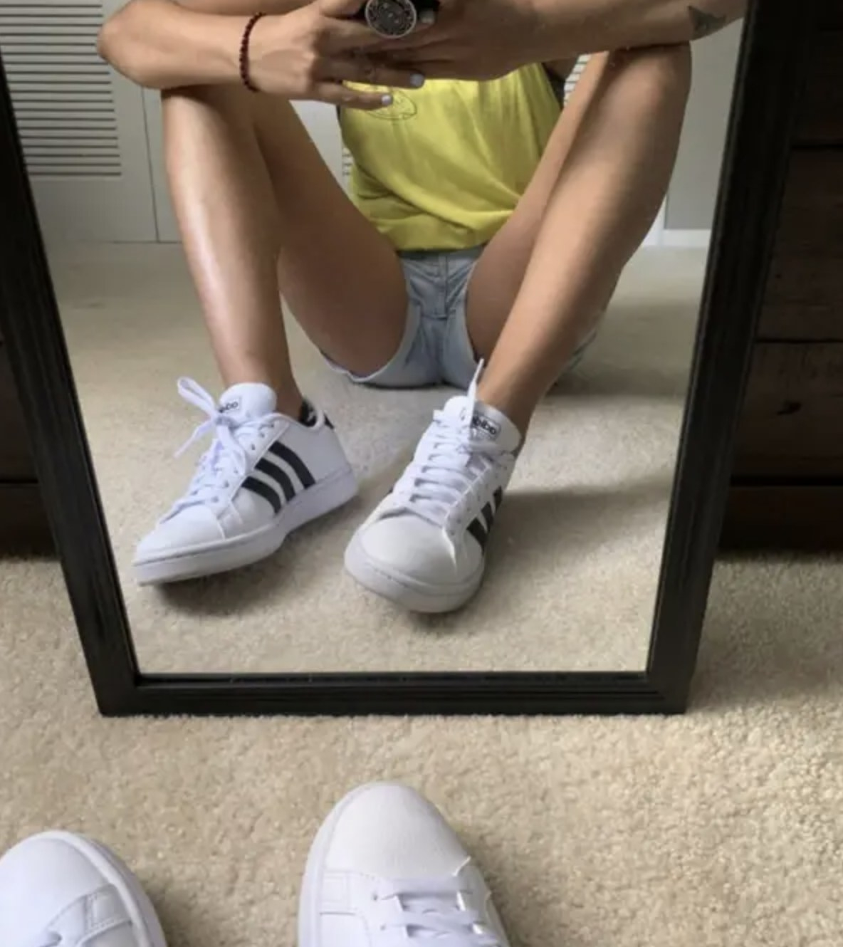 Person is wearing white sneakers with three black stripes on the sides