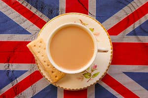A cup of tea and a biscuit sitting on top of a british flag