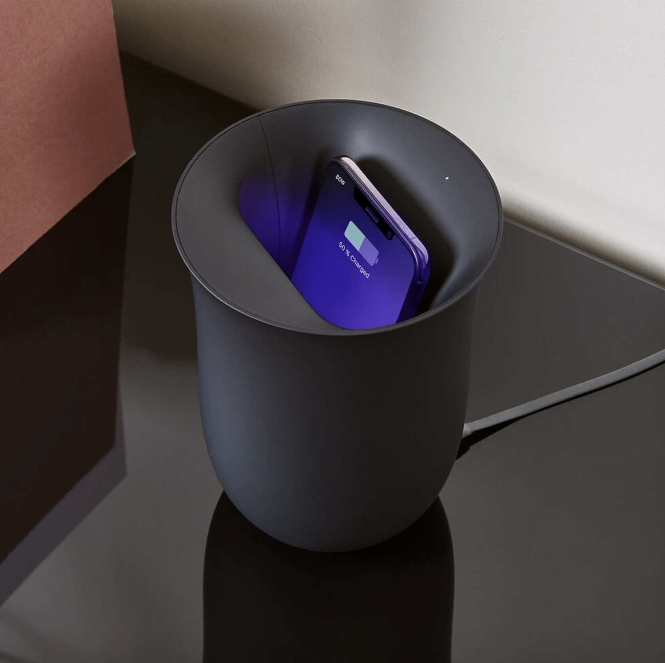 an iPhone charging inside of a black oblio phone sanitiser and wireless charger