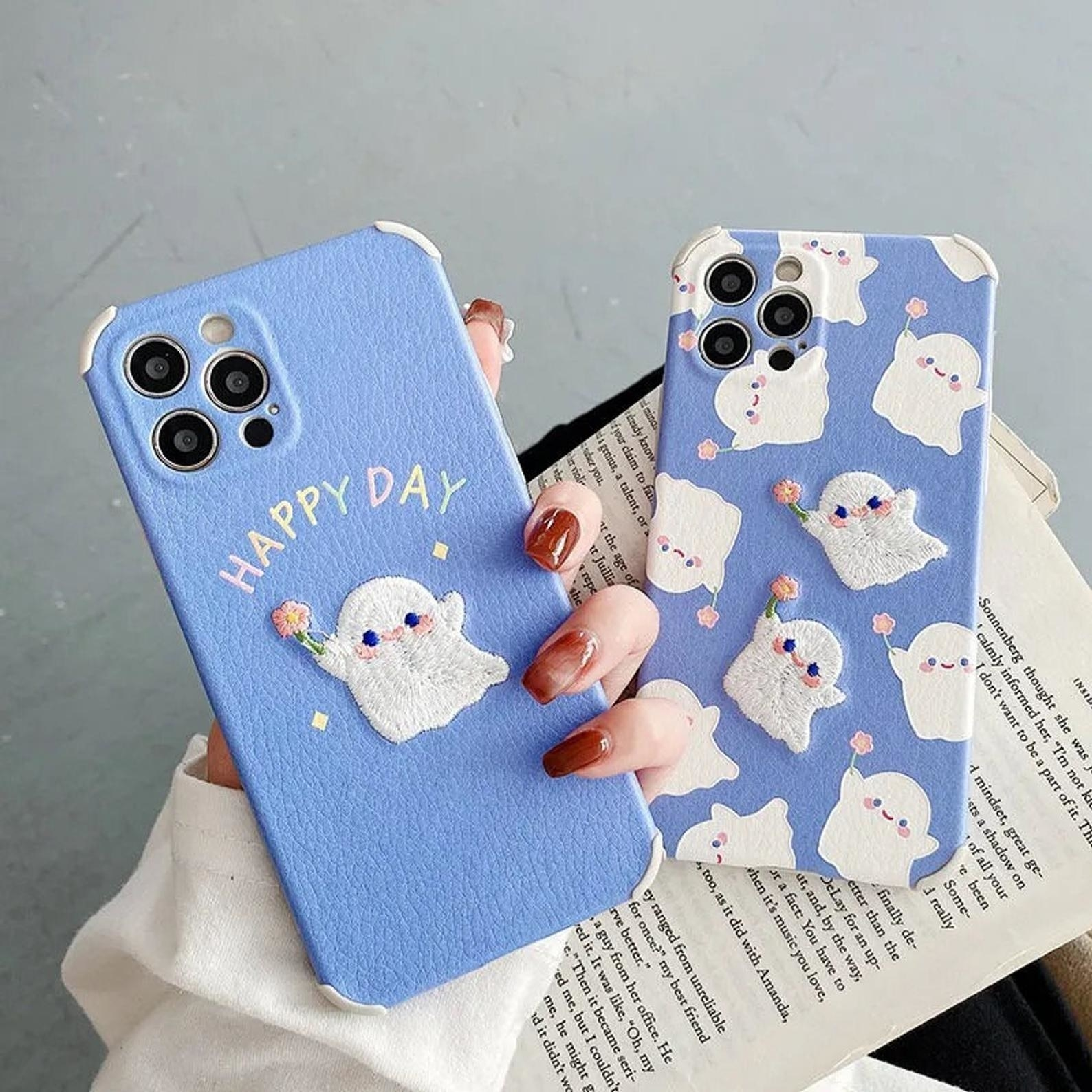 two blue phone cases with little ghosts holding flowers embroidered on them
