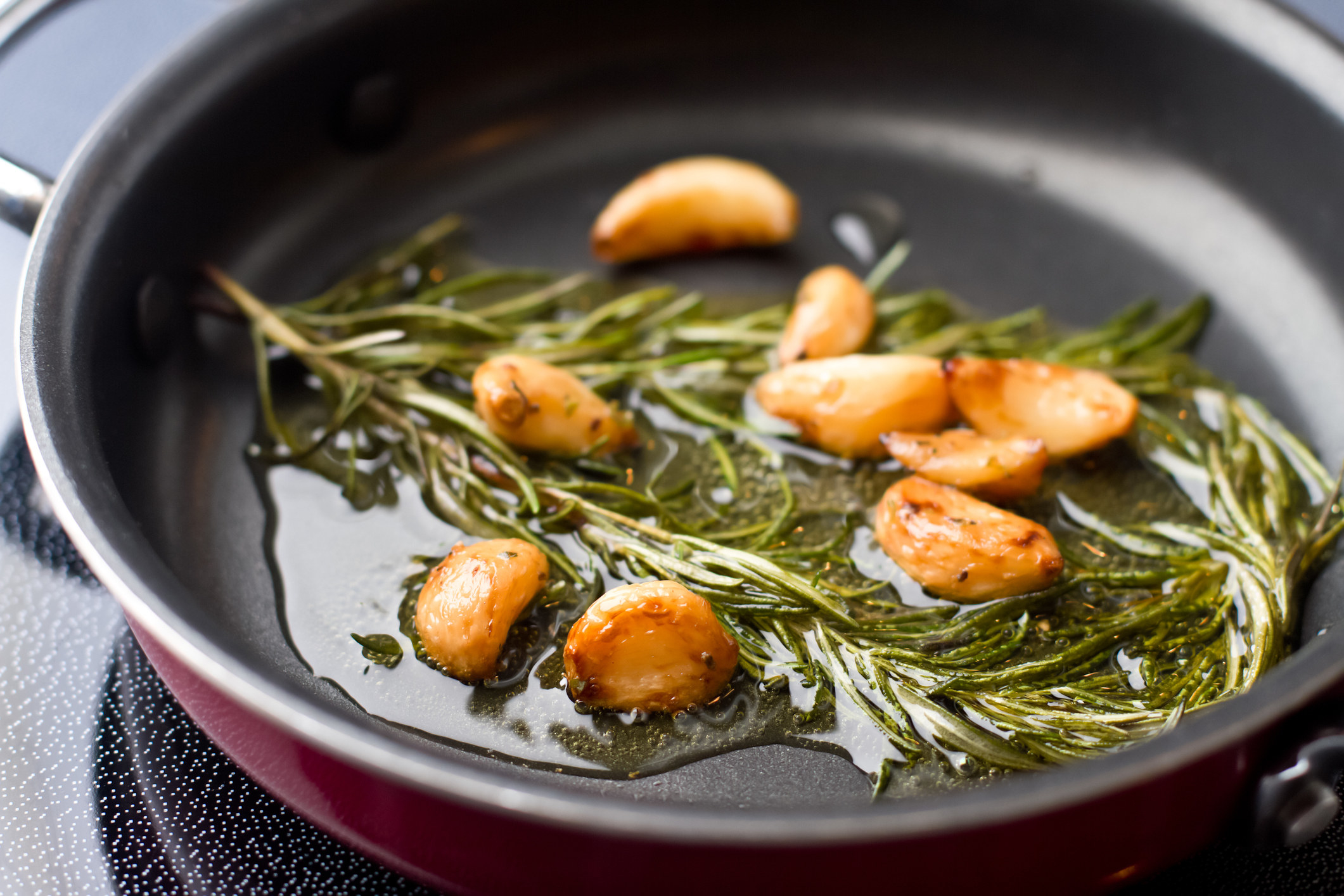 Garlic cloves and rosemary cooking in olive oil.