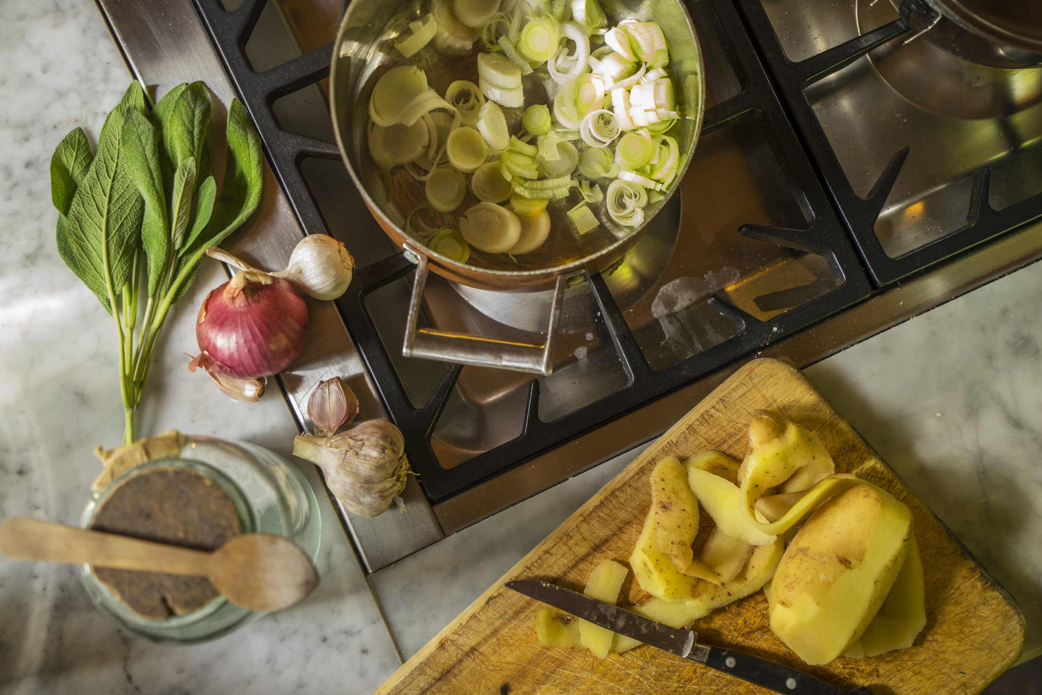 Cooking leeks and potatoes on the stovetop.