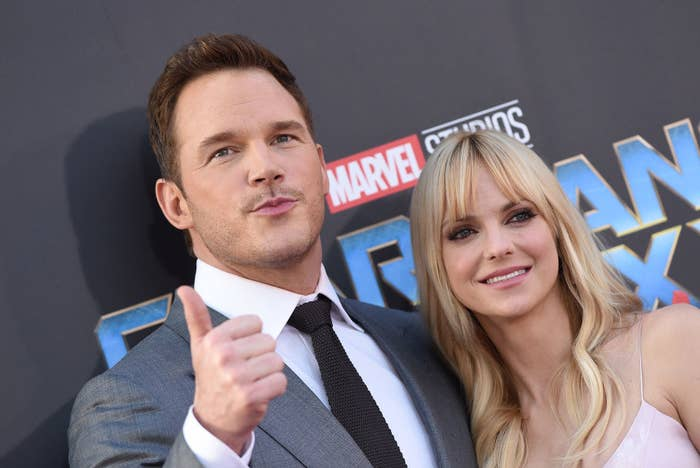 Chris giving a thumbs up as he poses with Anna on a red carpet