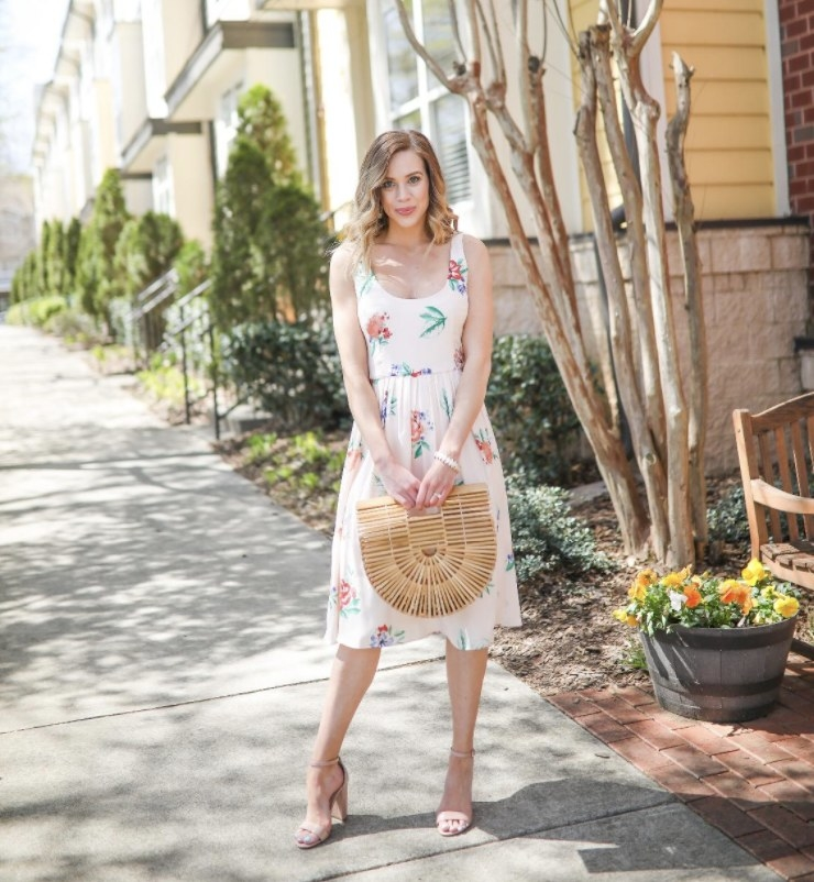 Person is wearing a white floral dress and holding a bamboo handbag