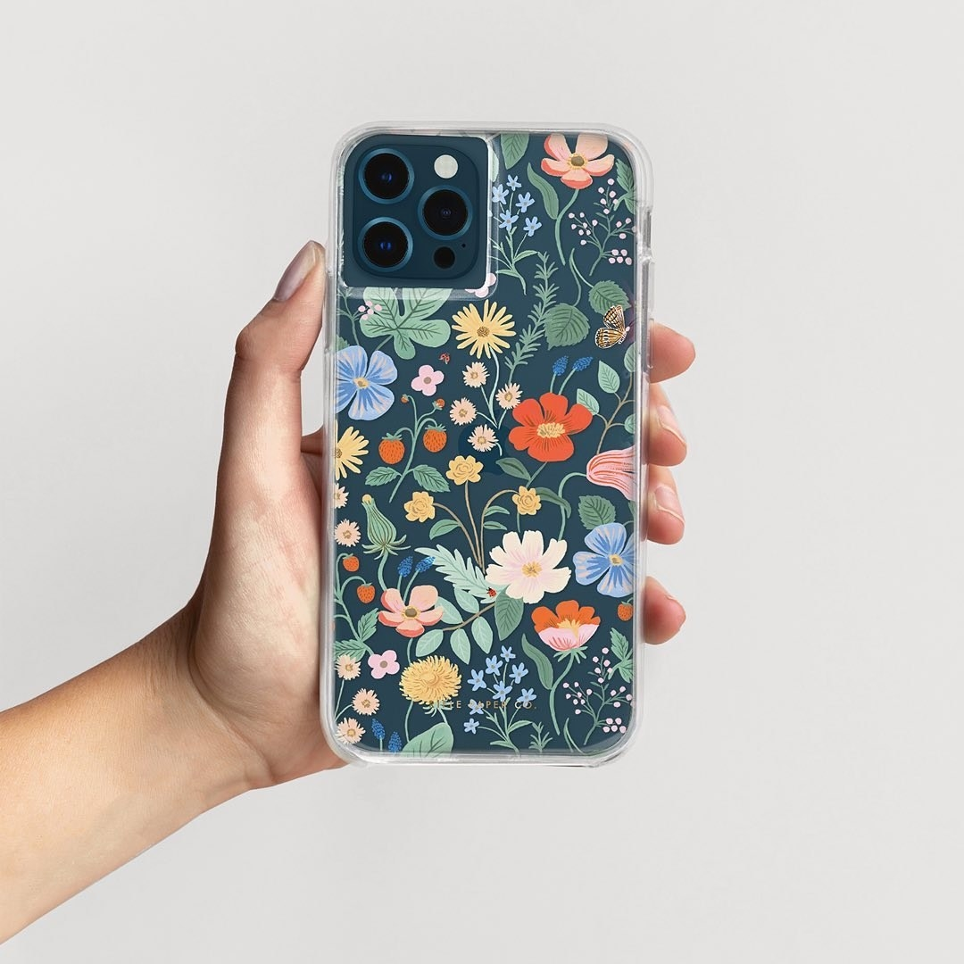 a model holding a phone with a clear phone case filled with florals