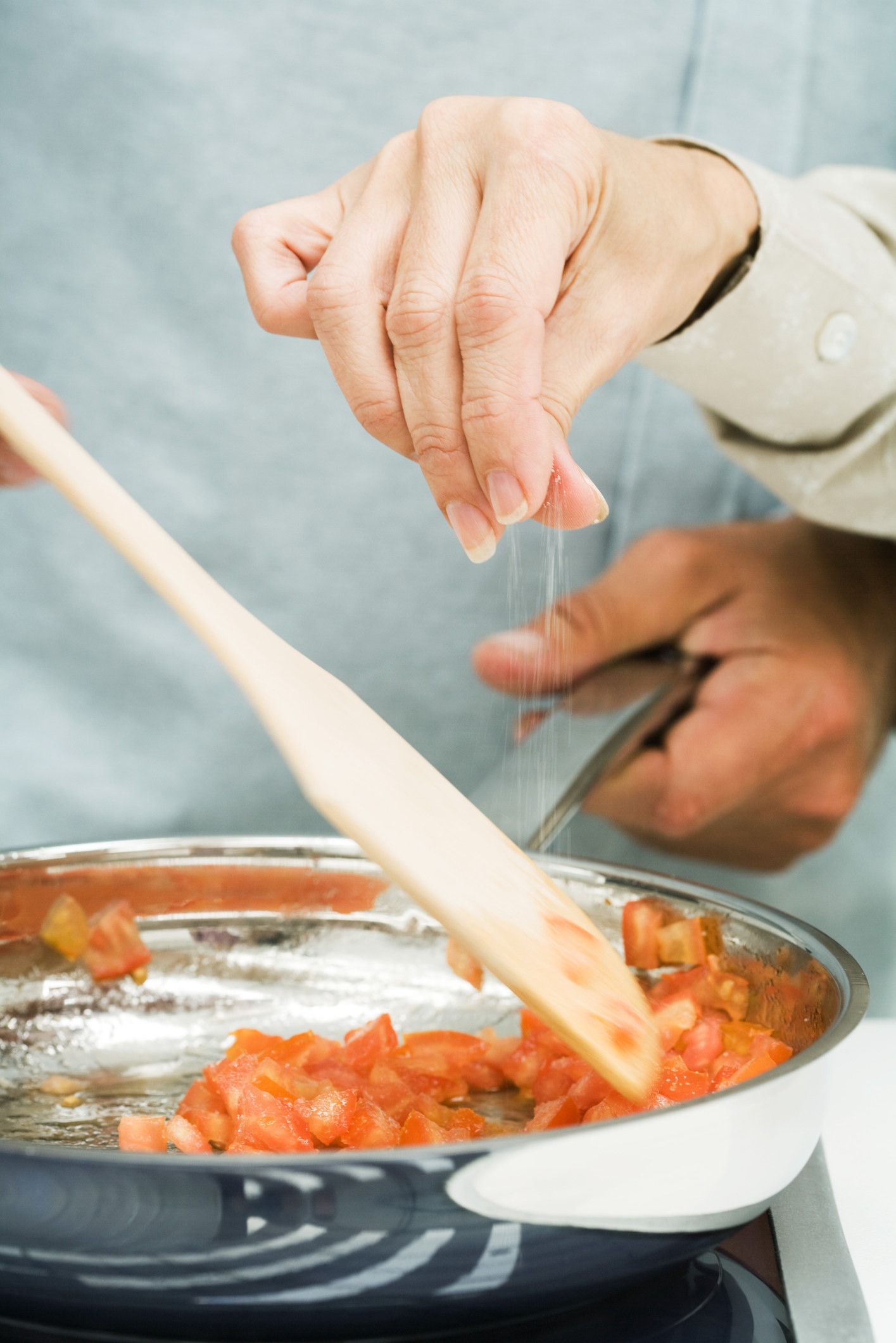 A woman salting vegetables in a skillet.