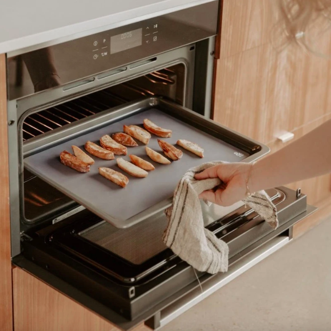 Someone taking a baking sheet out of the oven that's lined with the silicone mat