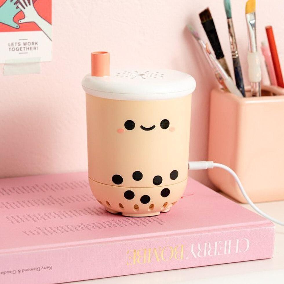 the pearl boba tea air purifier atop a big pink book