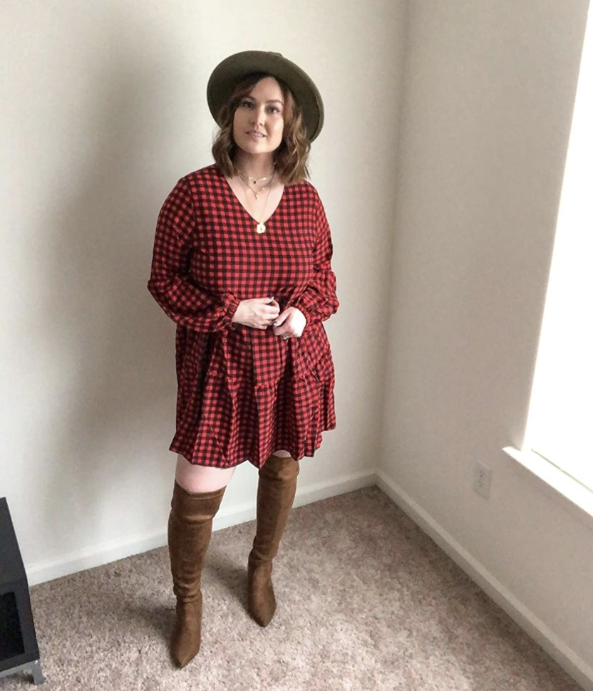 Person is wearing a red and black checkered dress with brown boots and a black hat