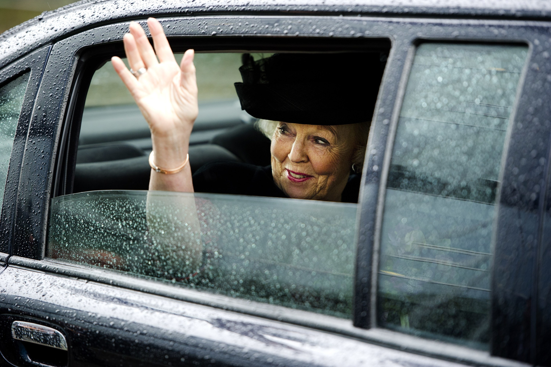 Queen waving out of a sleek black car