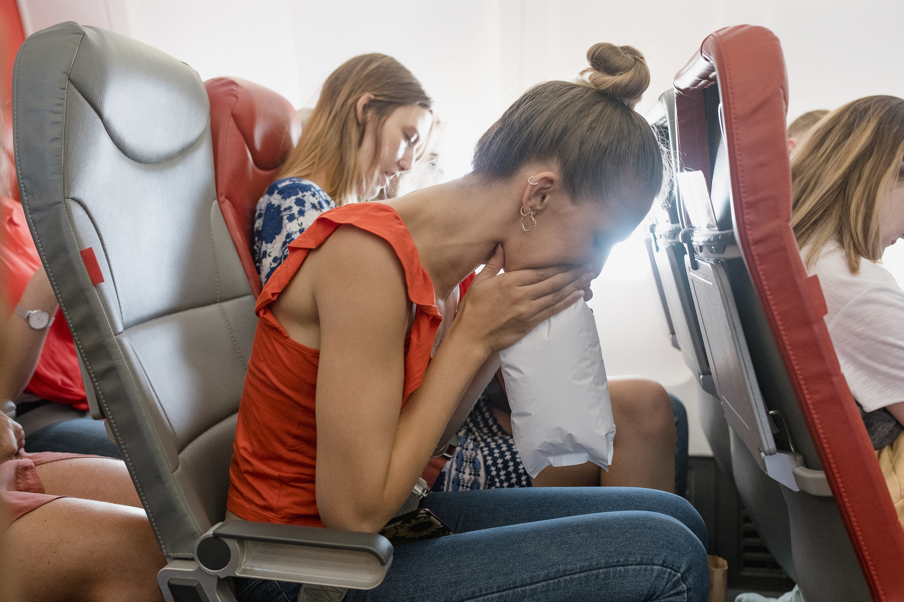 Young woman breathing into a vomit bag while seated in economy class seat
