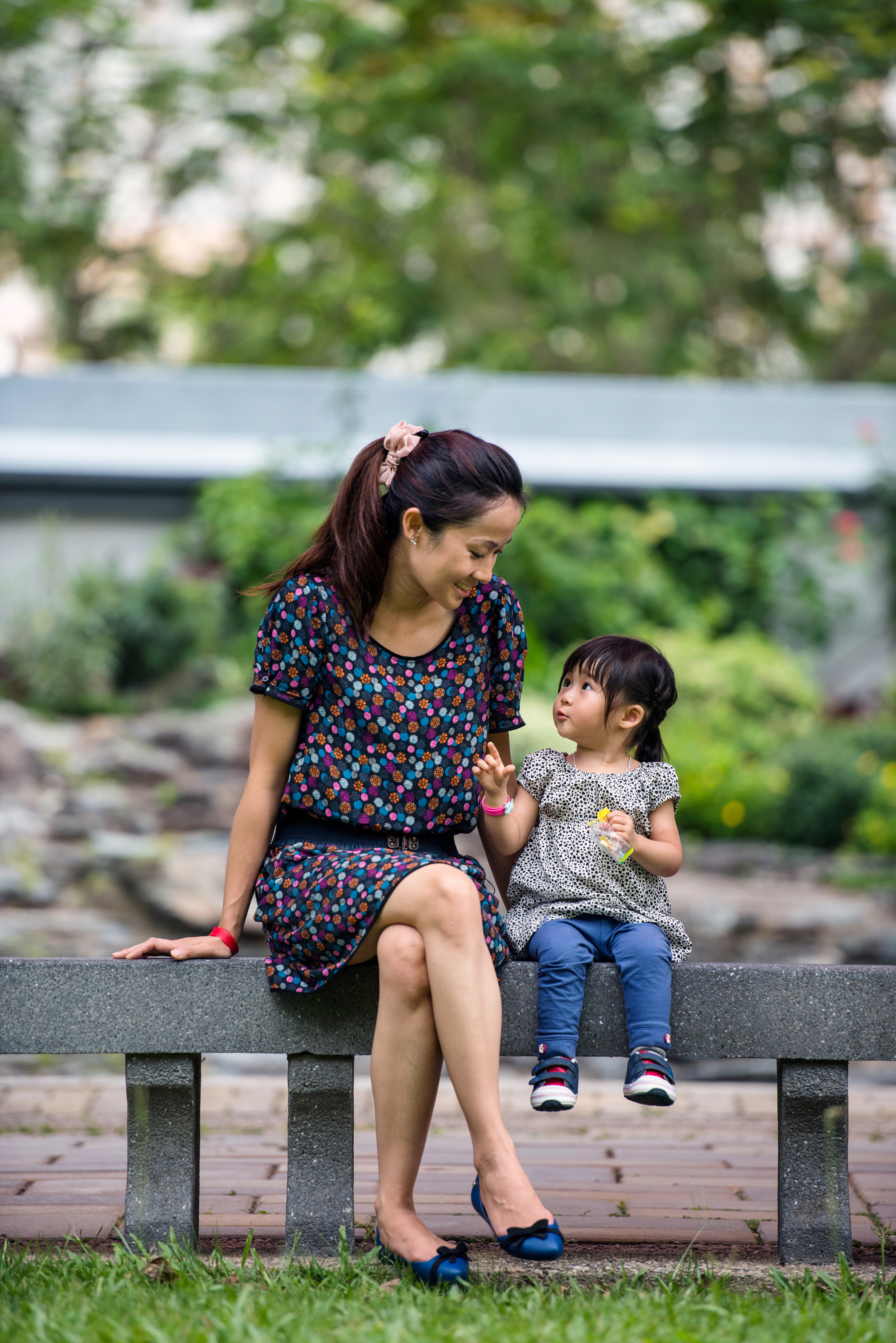 Asian mother talking to her toddler, while sitting on a stone bench in the park