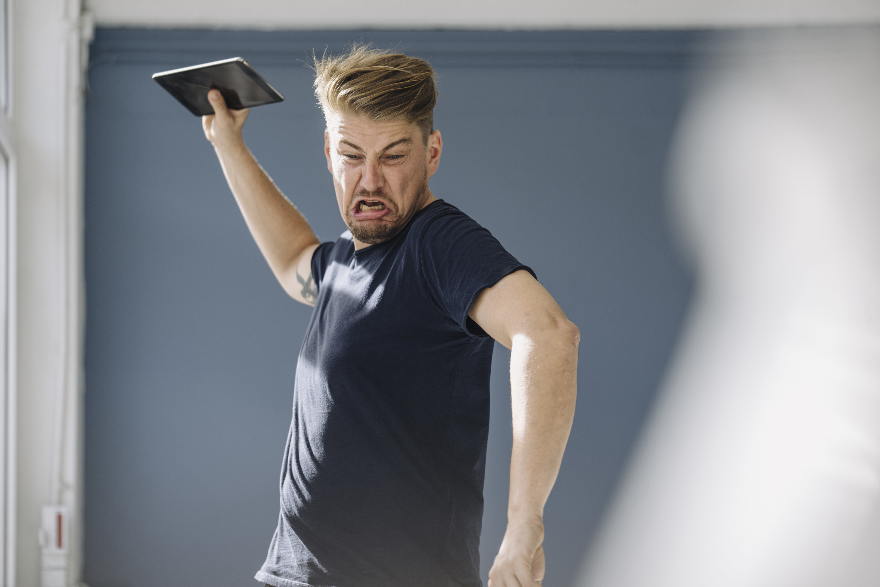 Angry man throwing his tablet on the floor