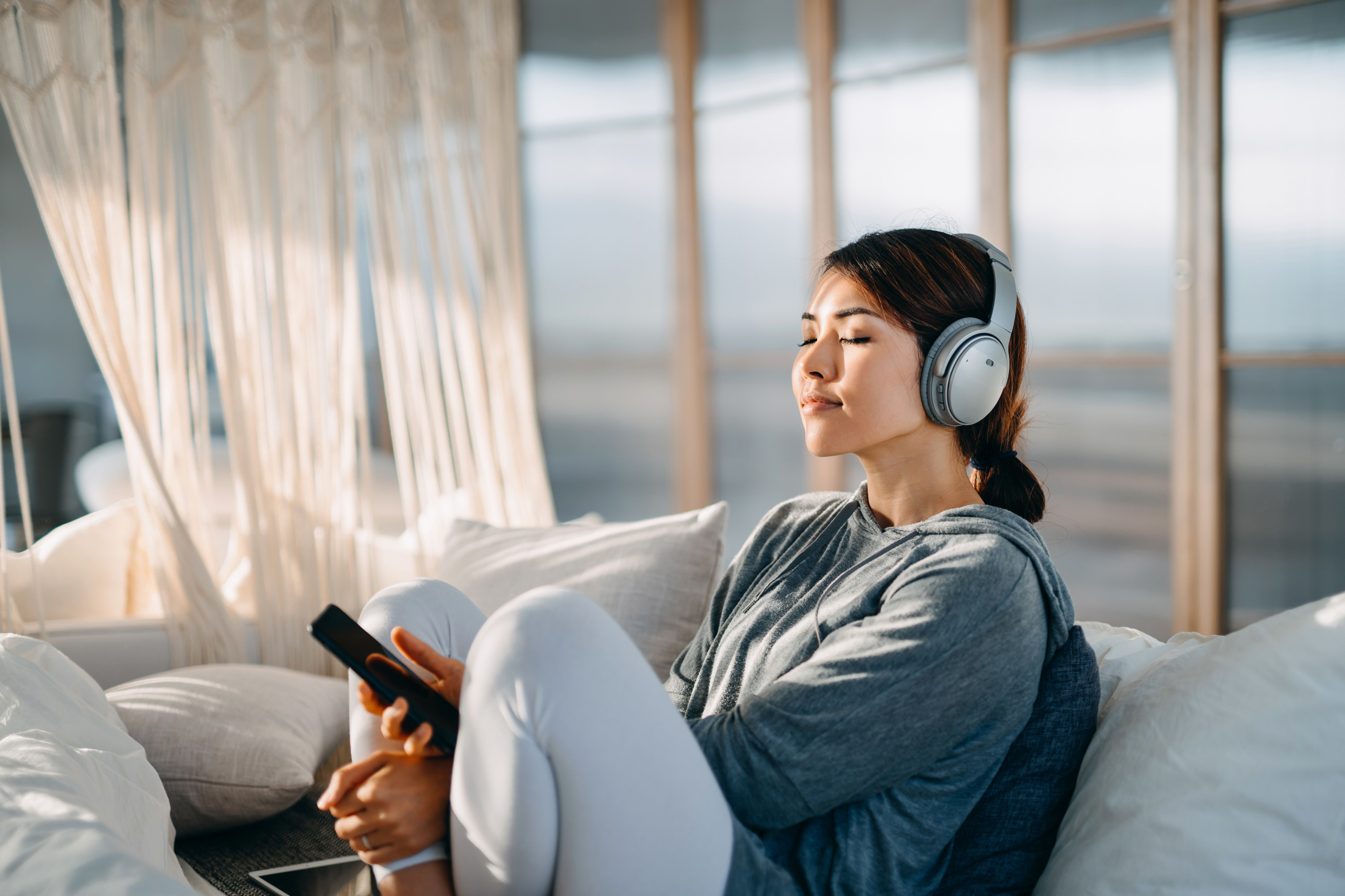 Younger woman listening to music on headphones, while sitting on a white sofa in breezy-looking room