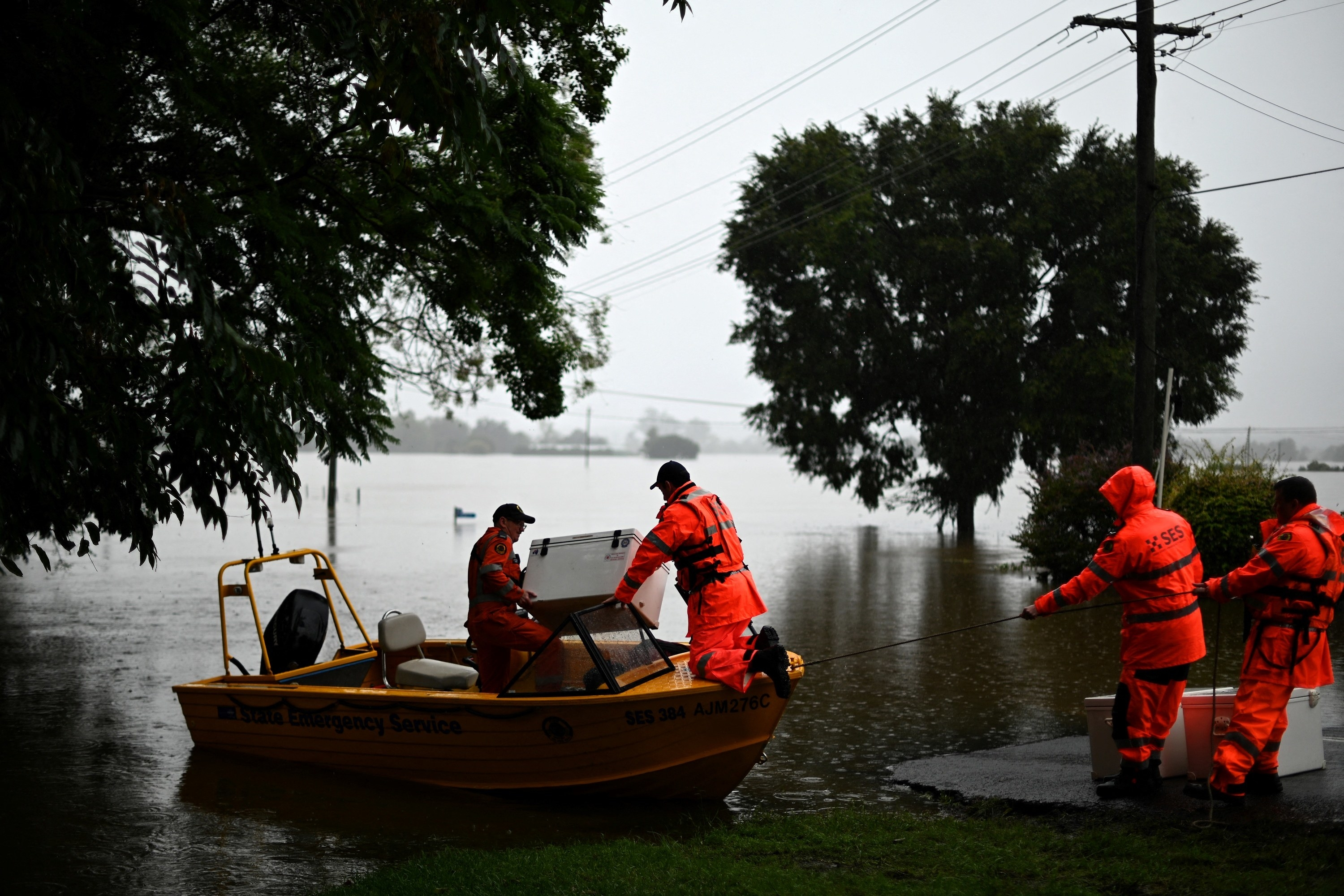 Four men in dry suits hold a boat in place and lift a cooler off of the boat in a flooded area