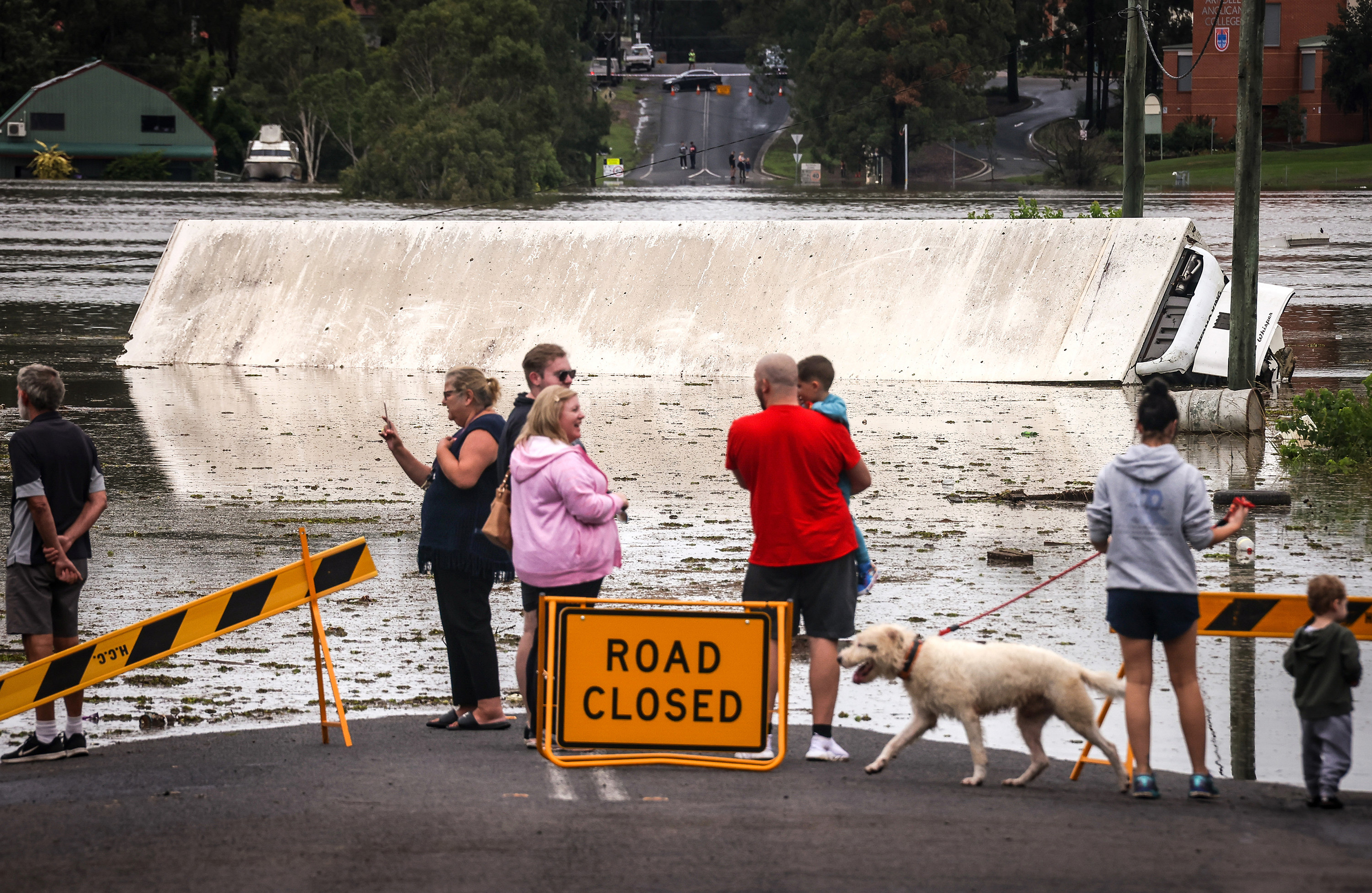People gather at the end of a flooded area, with road closed signs, to take pictures of a tipped over truck