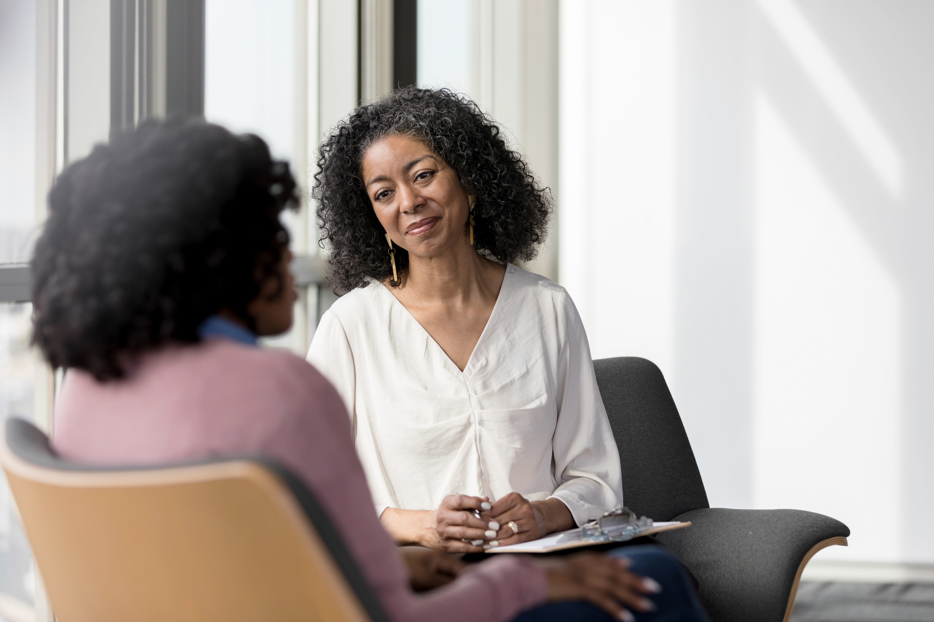 A Black therapist smiling calmly at a patient, who has her back turned to the camera