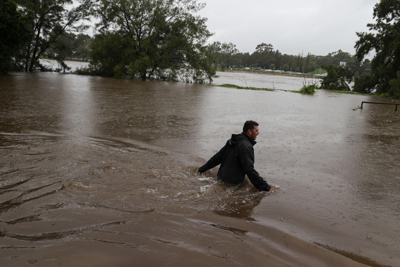 A man wades through waist deep floodwater