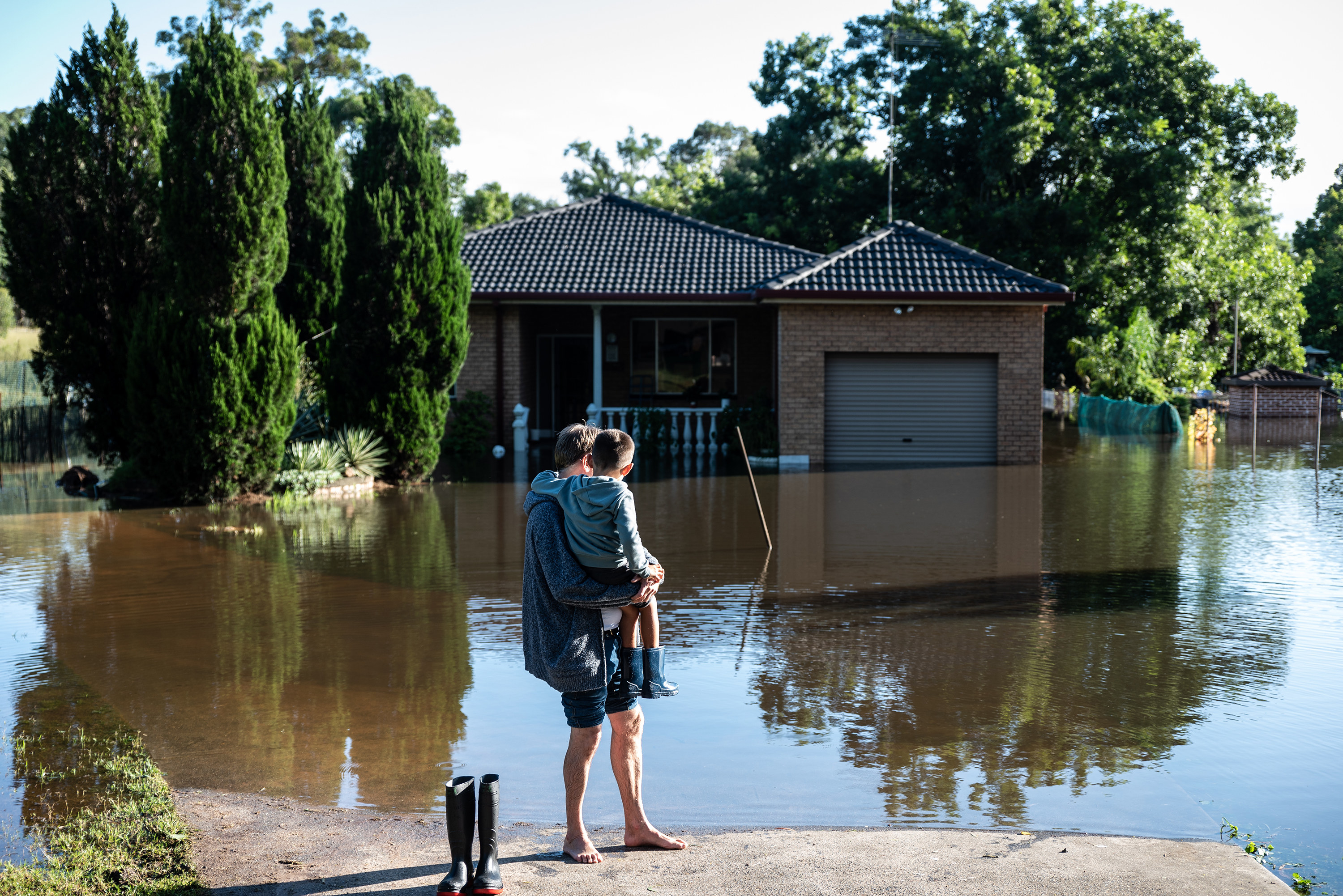 A father and son stand on dry land in front of a flooded home