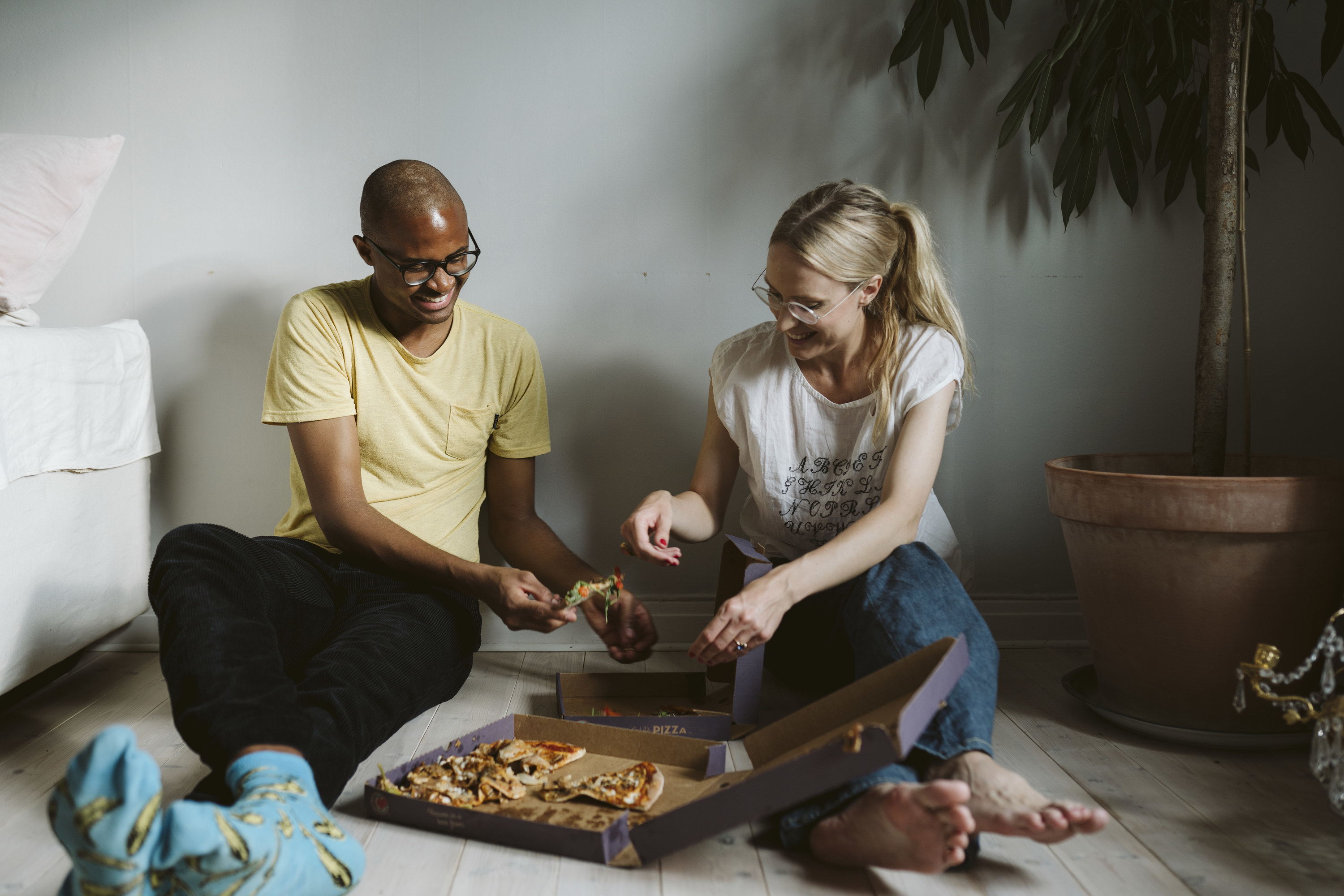 Two partners sitting on floor while eating delivery pizza out of a box