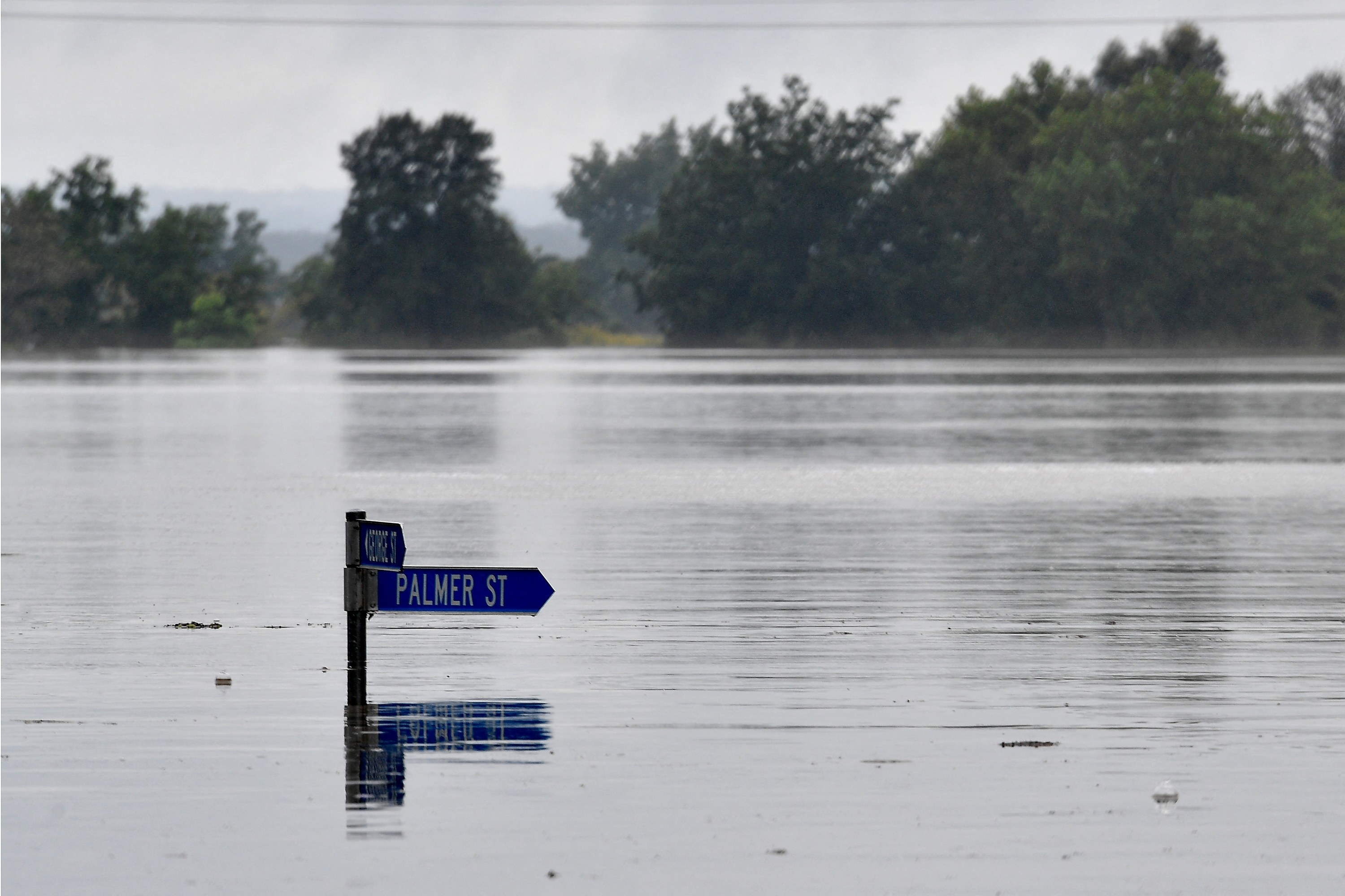 "A street sign that reads ""Palmer Street"" is just visible above a flooded residential area."
