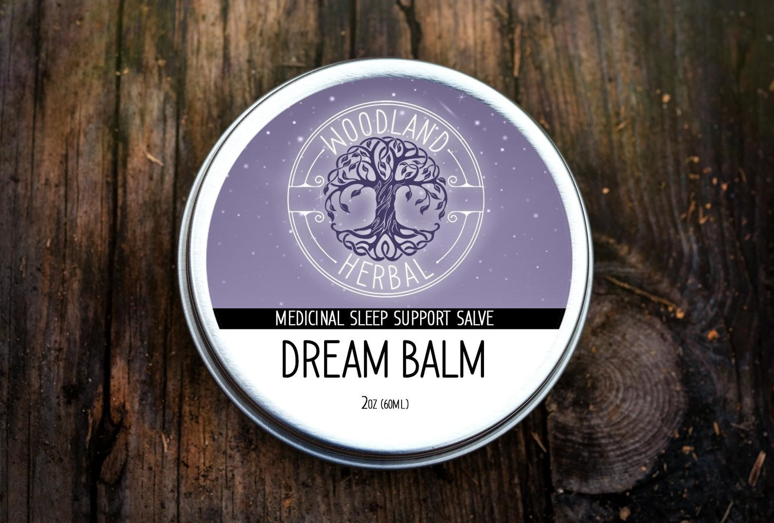 a tin of the dream balm in silver, white, and purple packaging