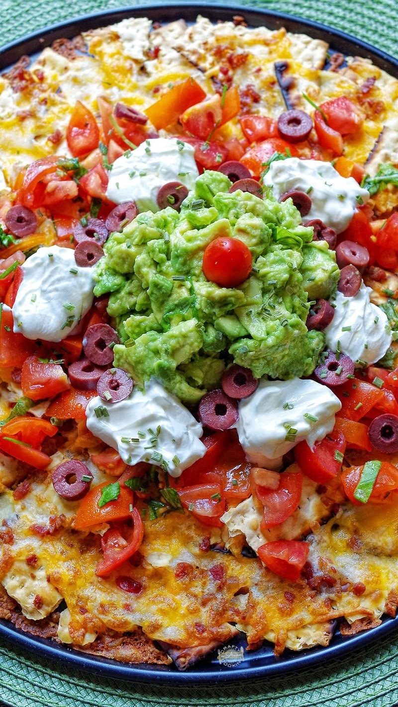 Matzo nachos with tomatoes, olives, guacamole, and sour cream.