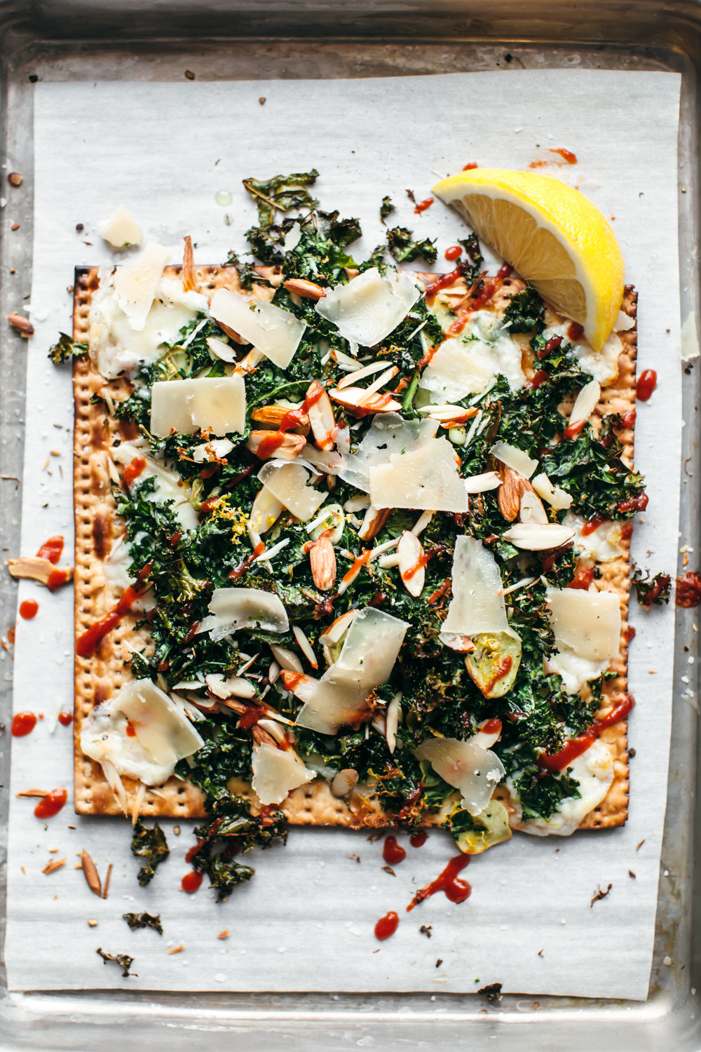 Matzo pizza with kale, Parmesan, and almonds.