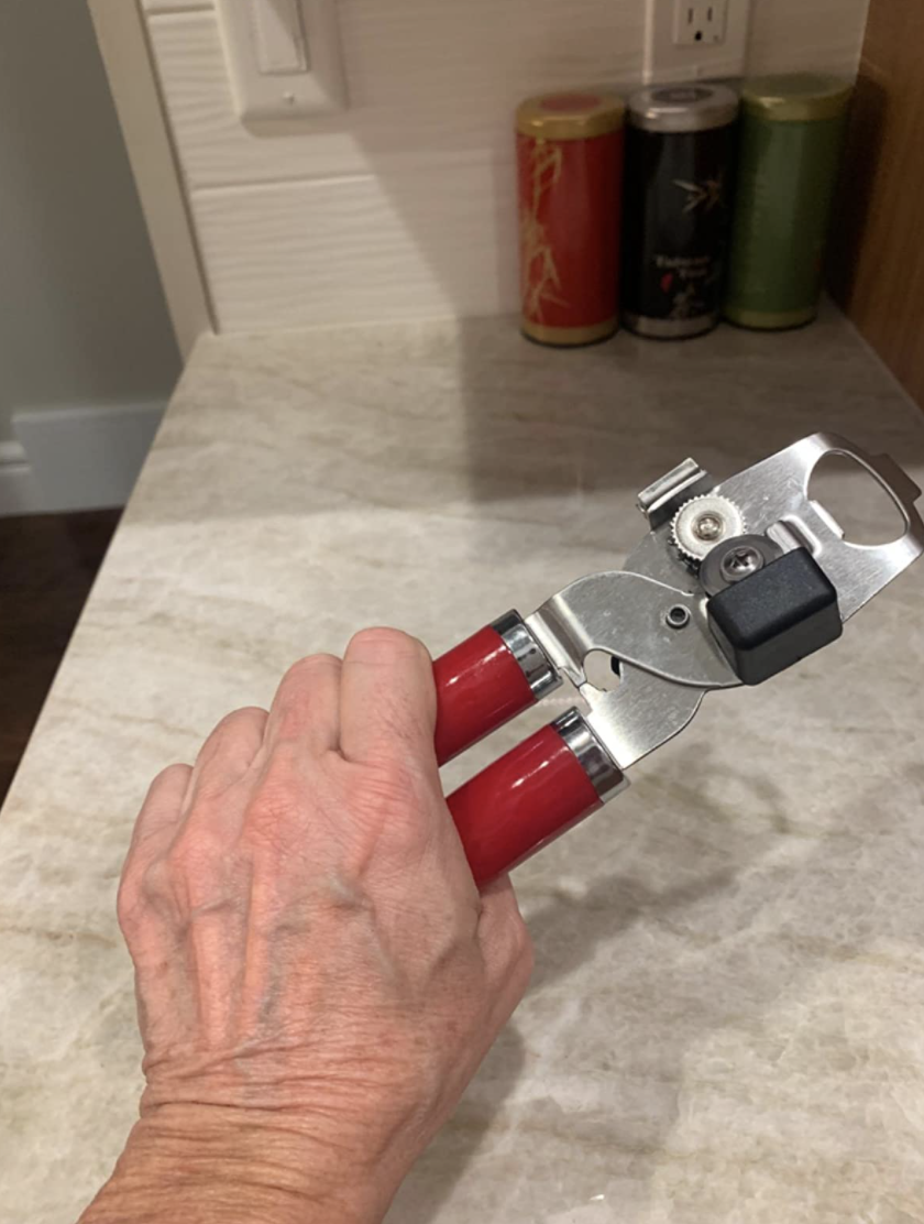 A reviewer holding the can opener