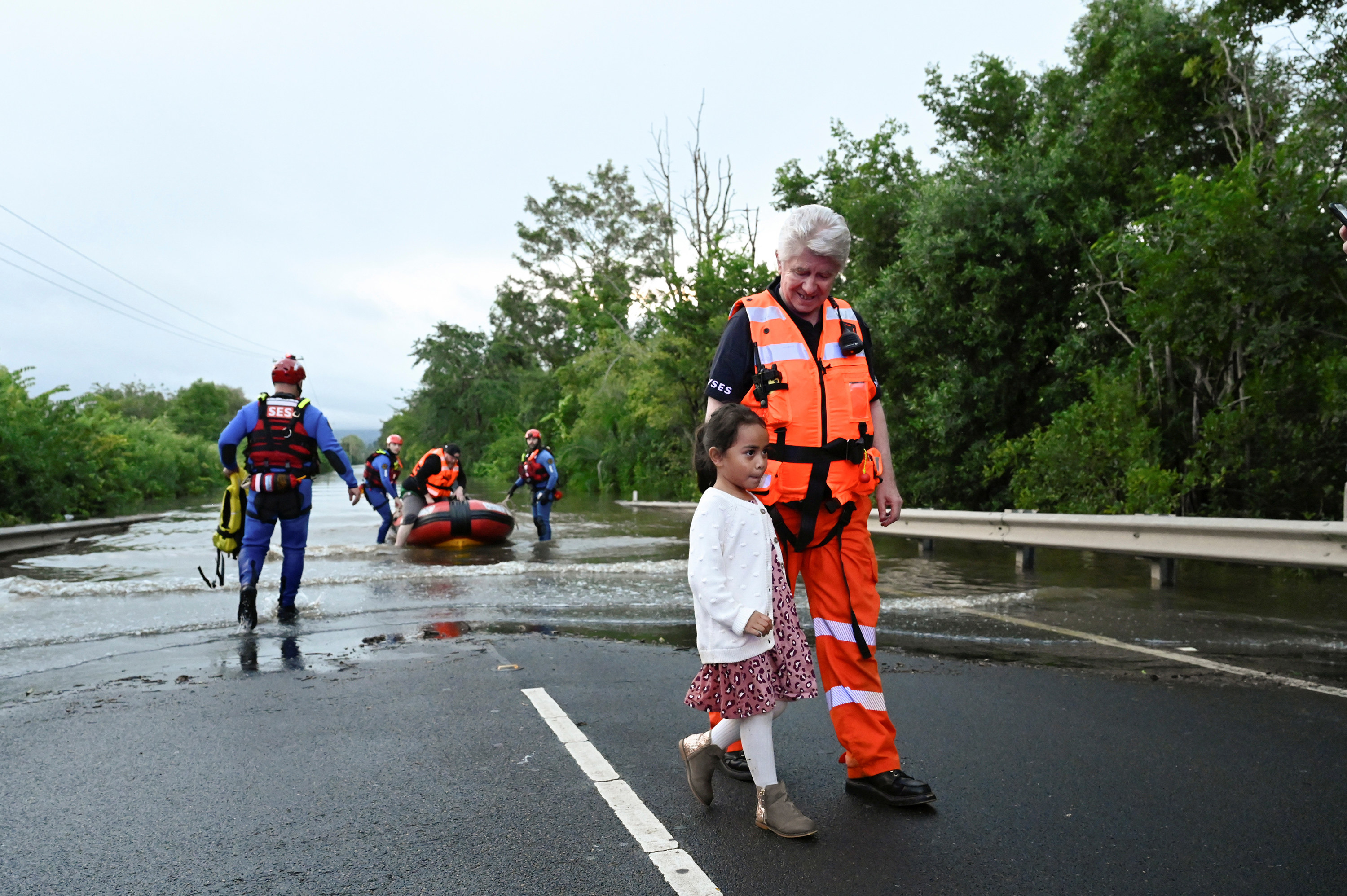 A woman in a drysuit escorts a young girl away from floodwater, behind them two workers assist a man getting out of the boat