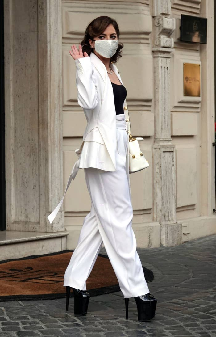 Lady Gaga waving as she walks out of a building in extremely high platform heels