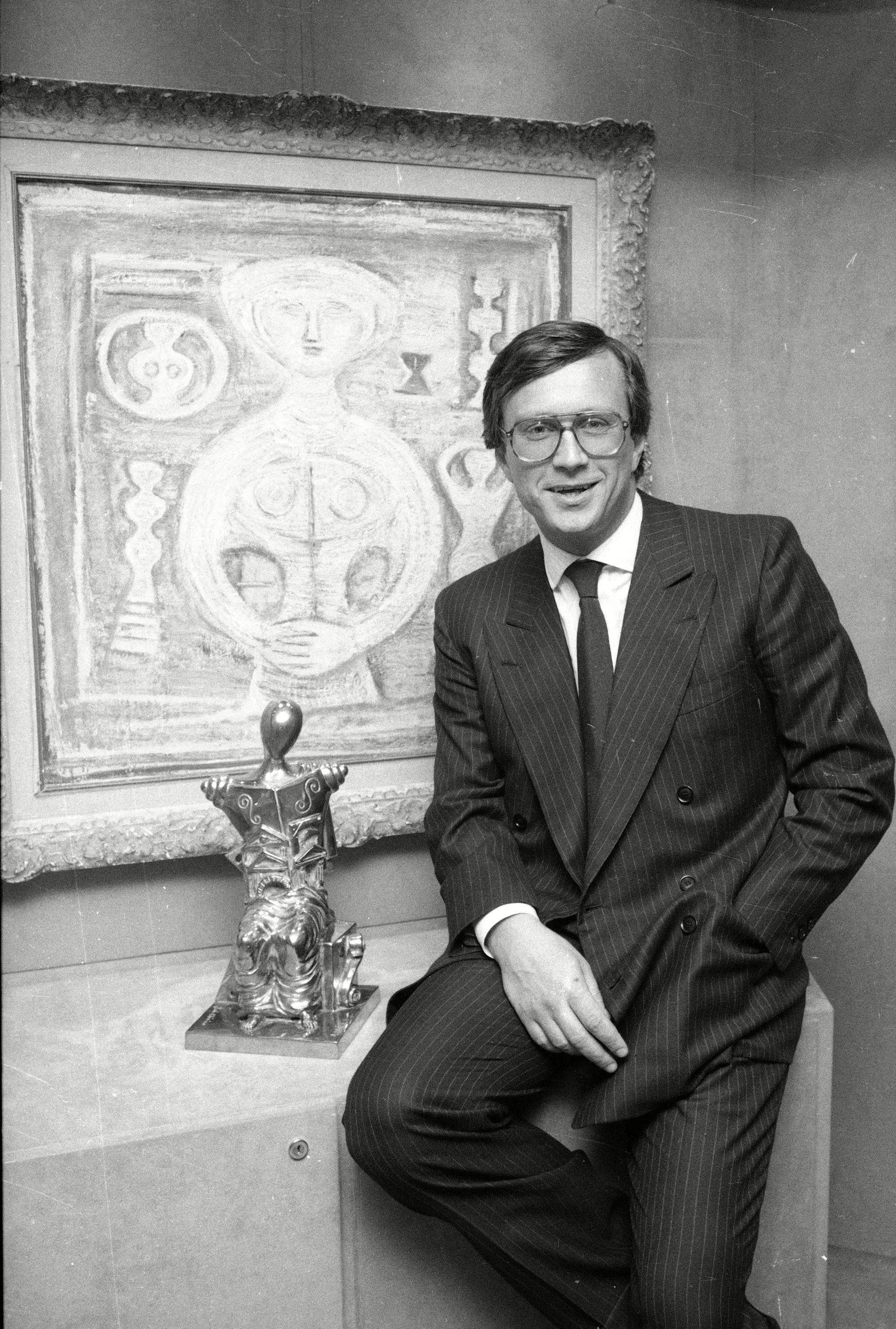 Maurizio posing in a pinstriped suit and eyeglasses