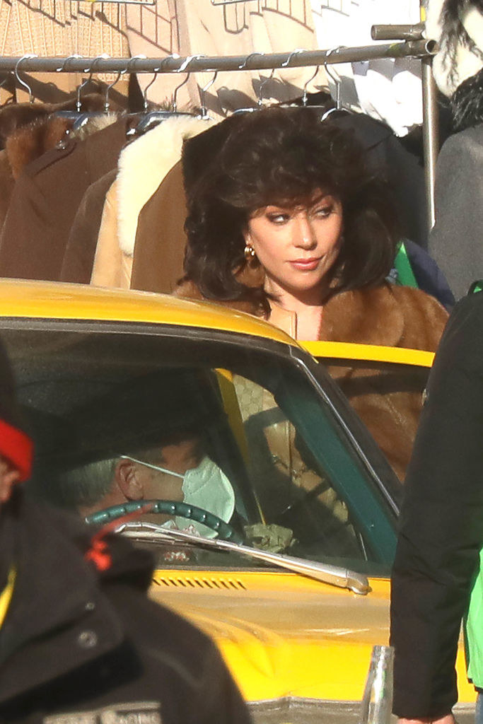 Lady Gaga standing next to a car and rocking teased black hair