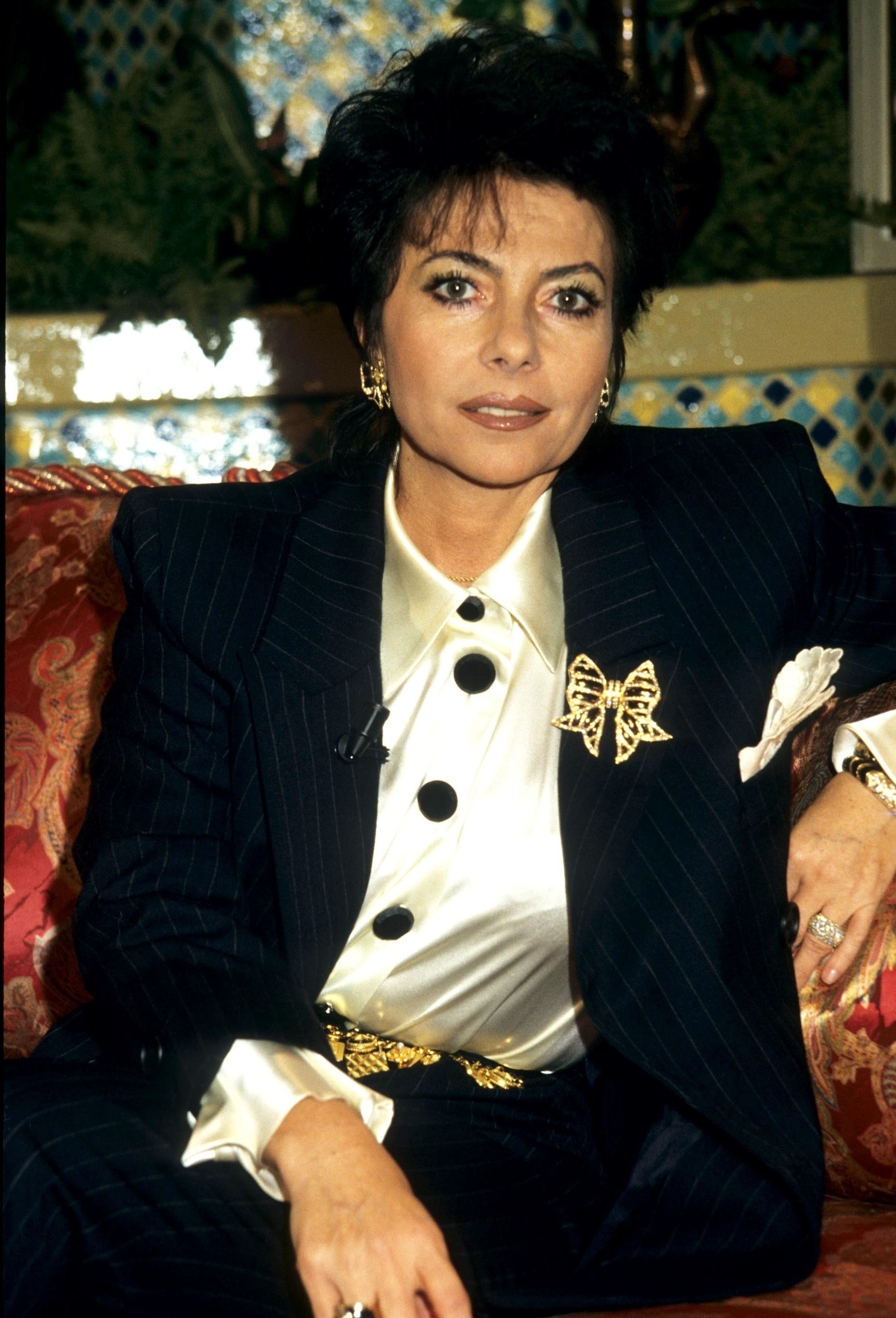 Patrizia wearing a suit as she sits on a couch