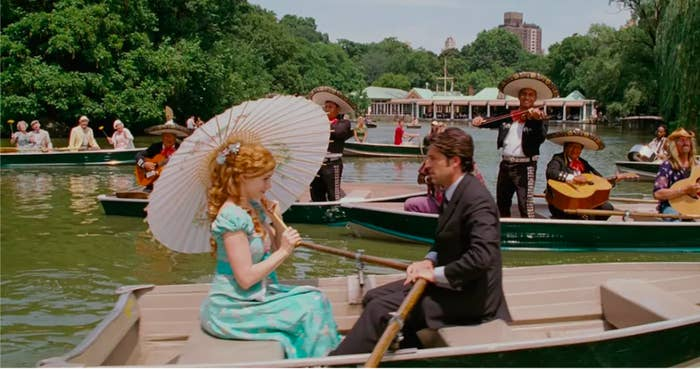 Giselle, Robert, and members of a mariachi band sit in row boats