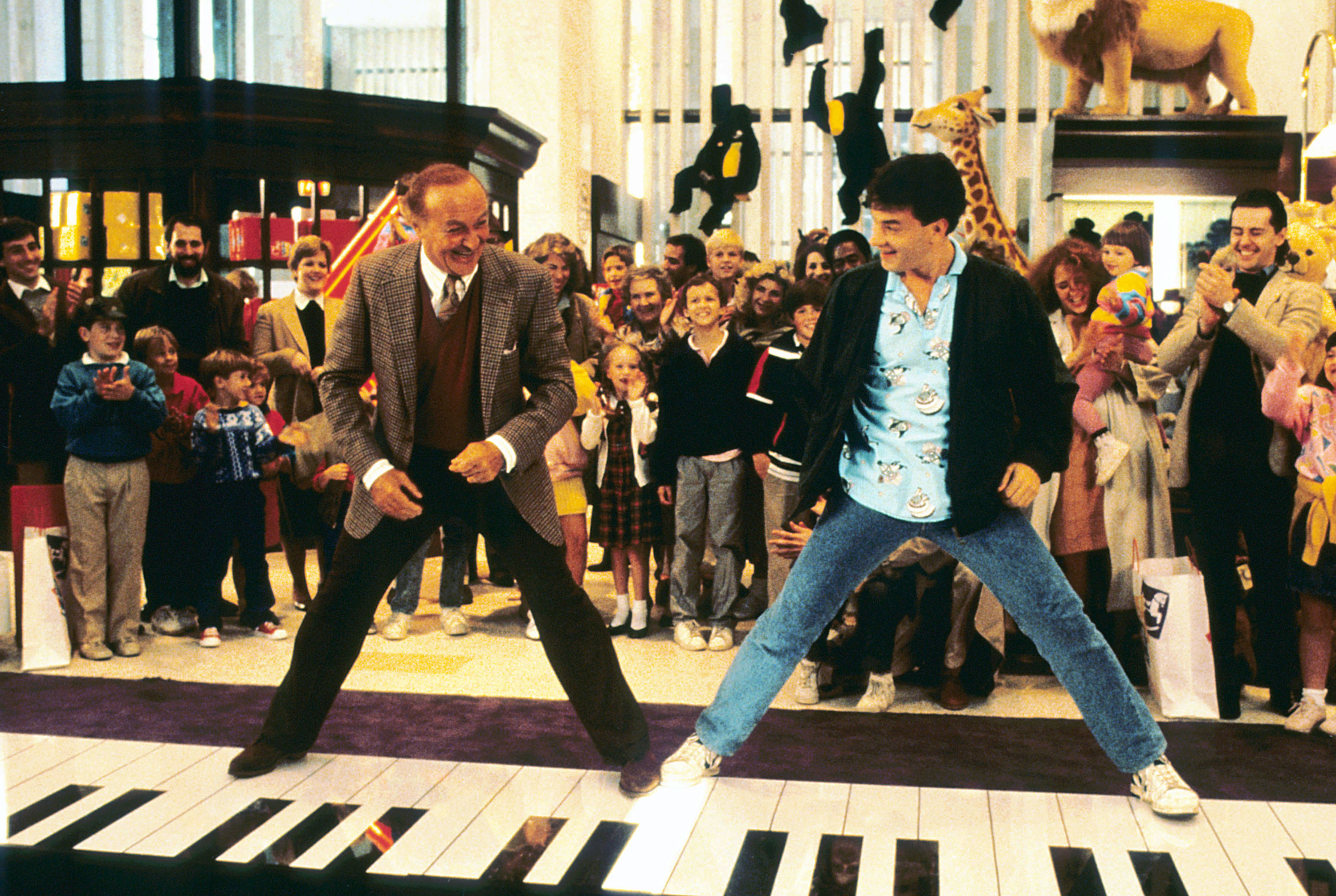 Two men stand widely on a large piano rolled out over the ground