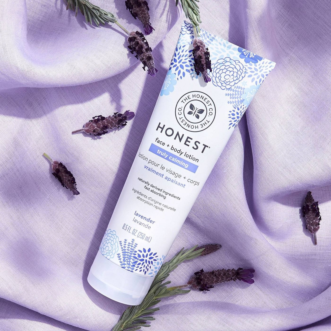 A bottle of lavender face and body lotion on a purple backdrop