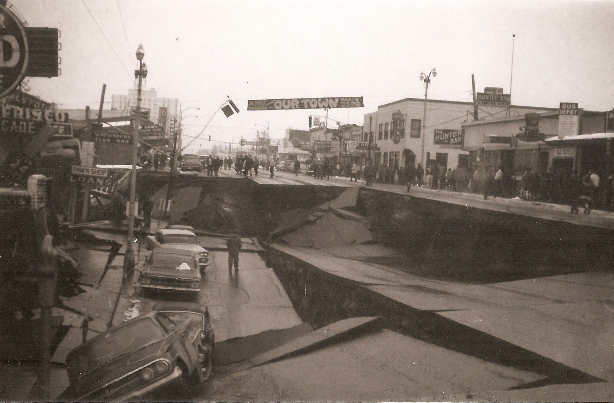 A destroyed street with a banner hanging over that says Our Town