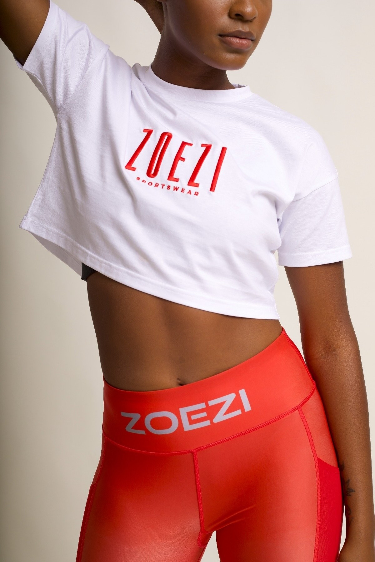 """model in white cropped tee that says """"zoezi sportswear"""" on the front"""