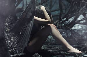 A fairy with dark black wings clutching her head