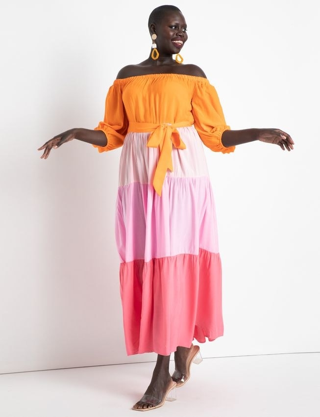 model in the ankle-length, tie-waist, pink, orange, and coral dress with three-quarter sleeves