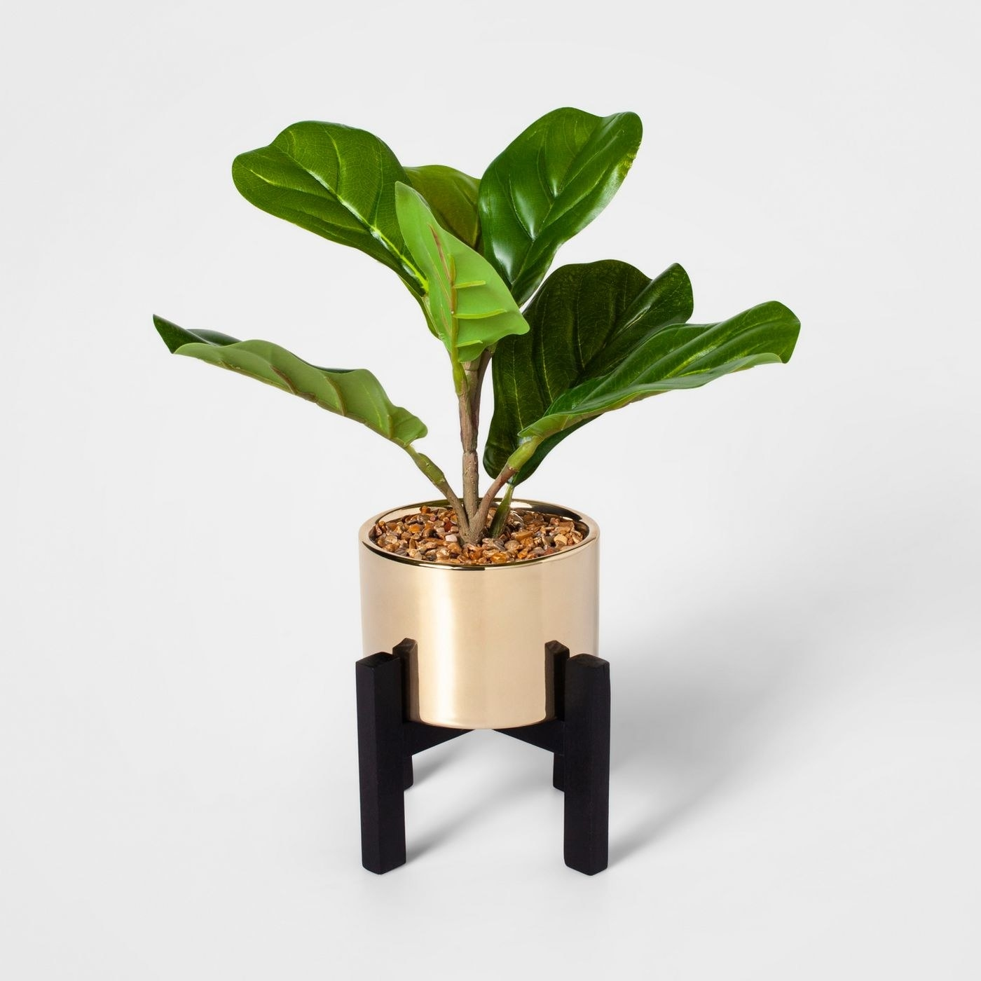 A faux fiddle leaf fig in a gold planter with black legs