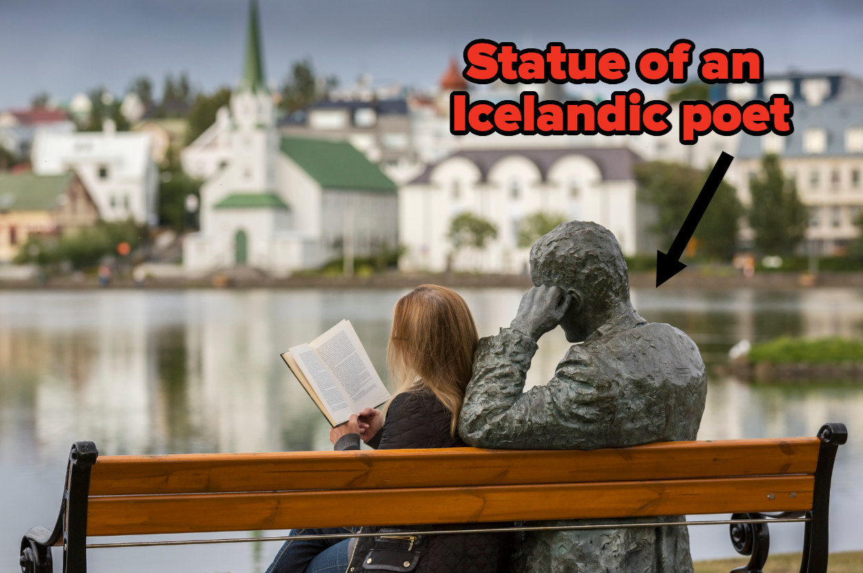 A woman sits on a bench overlooking Reykjavík next to a statue of an Icelandic poet