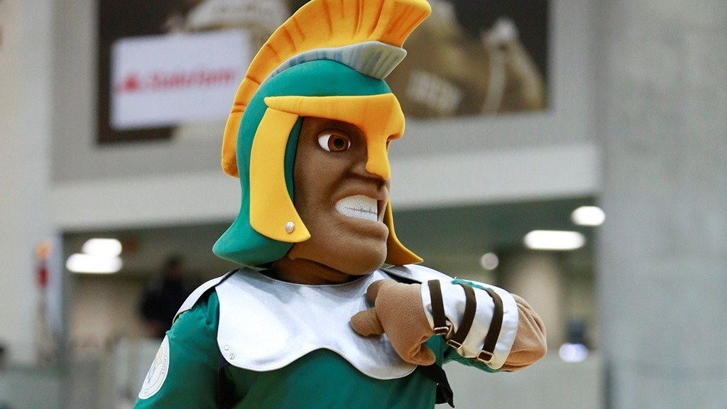 Spartans mascot pointing to himself.