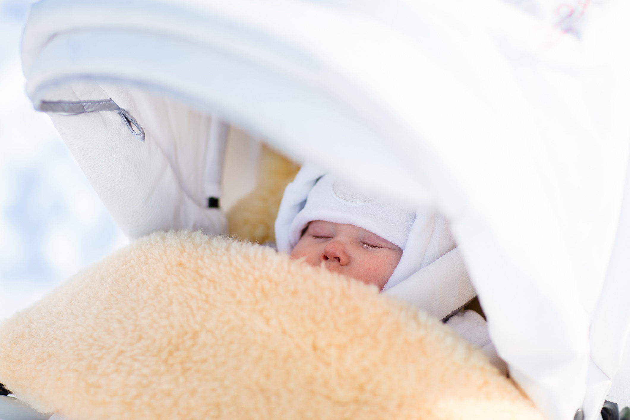 A baby bundled up in warm clothes and blanket sleeps inside of a stroller outside