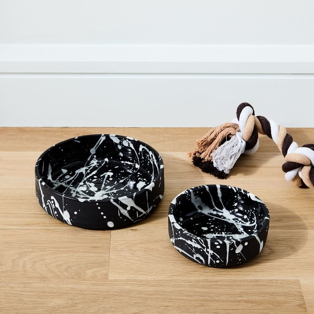 Two black bowls in different sizes with white splatter paint pattern