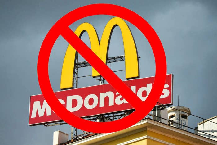 """A McDonald's sign against a gray sky with a superimposed red """"no"""" symbol over it"""