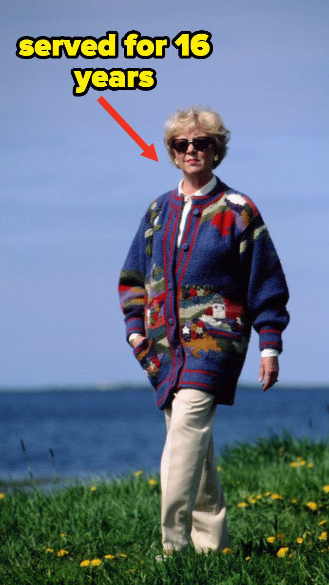 Vigdís Finnbogadóttir in a dated photo walks along a field of grass next to the water wearing a long cardigan and sunglasses