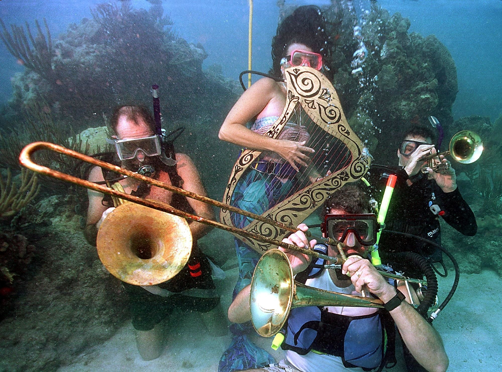 divers playing a harp, trumpet, and saxophone underwater